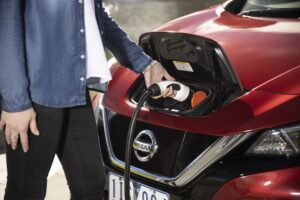 Man charging an electric vehicle