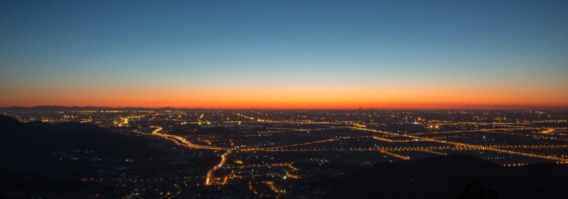Cityscape with orange glow on the horizon